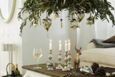 11 greenery chandelier topped with candles and with hanging silver ornaments