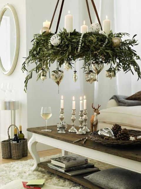 greenery chandelier topped with candles and with hanging silver ornaments