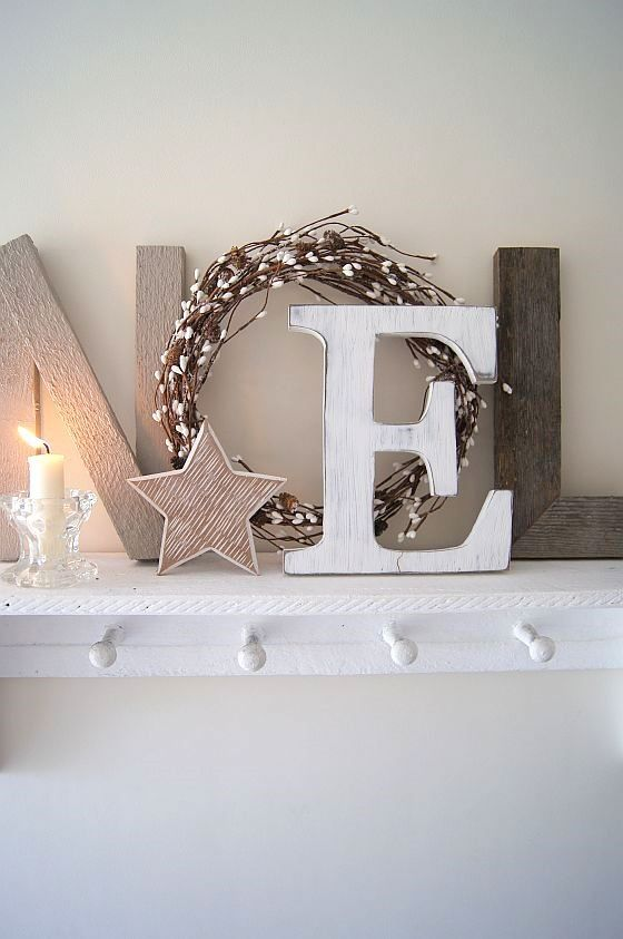 neutral Christmas mantel with letters, a candle and a star