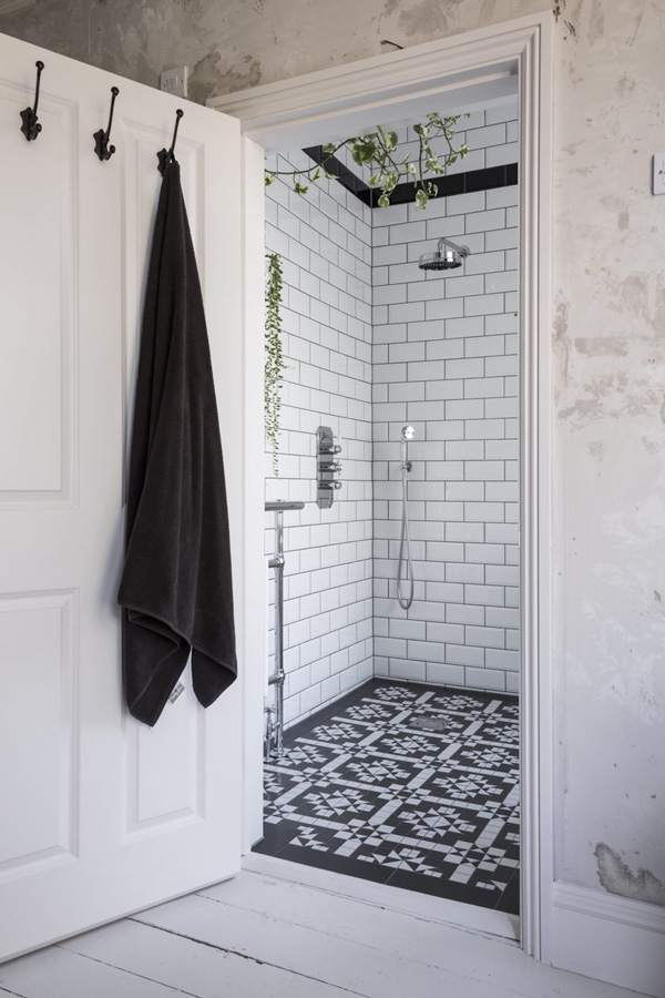 Black and white with fresh greenery make up the bathroom decor