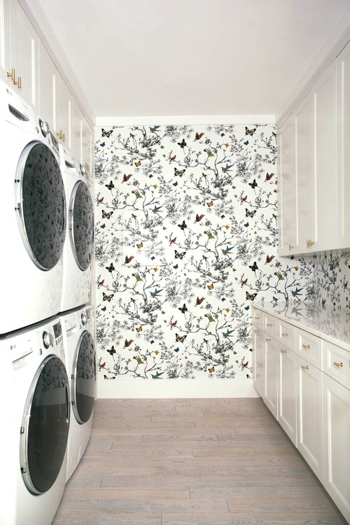 The laundry room is spacious and comfy, with flora and fauna print wallpaper