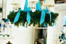 12 a usual chandelier covered with an evergreen wreath and turquouse ribbon