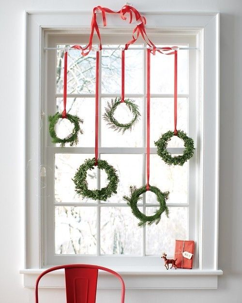 an assortment of small evergreen wreaths with red ribbon