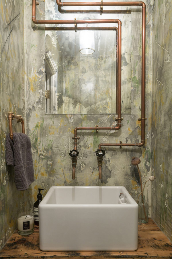 The sink space is covered with unique tiles that imitate a worn look