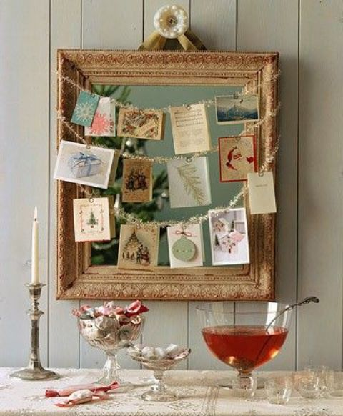 a framed mirror with garlands and  hanging photos and cards on them