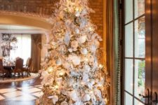 13 a large Christmas tree with white and silver decorations