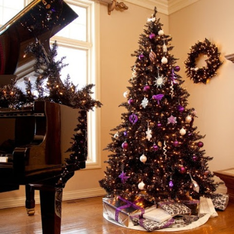 a wreath and  tree in black is chic and purple adds just the pop of color to this living room