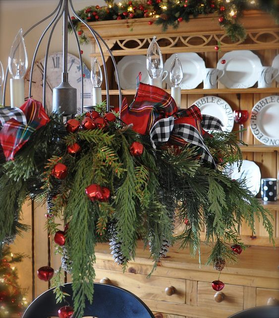 cute chandelier with plaid ribbon bows, fir branches and red jungle bells