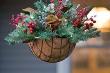 14 a hanging arrangement with evergreens, pinecones, berries and leaves