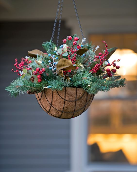 a hanging arrangement with evergreens, pinecones, berries and leaves