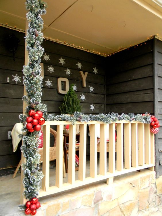 faux evergreen banister decor, red ornaments and snowflakes on the wall
