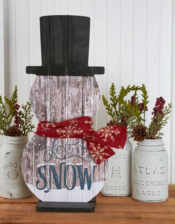 painted snowman-shaped sign 'Let It Snow'