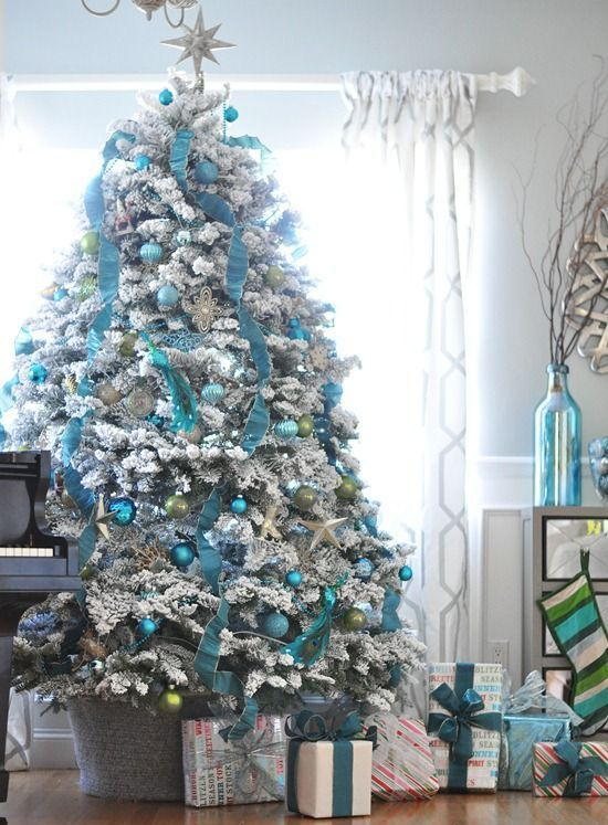 turquoise ornaments and garlands on a flocked Christmas tree