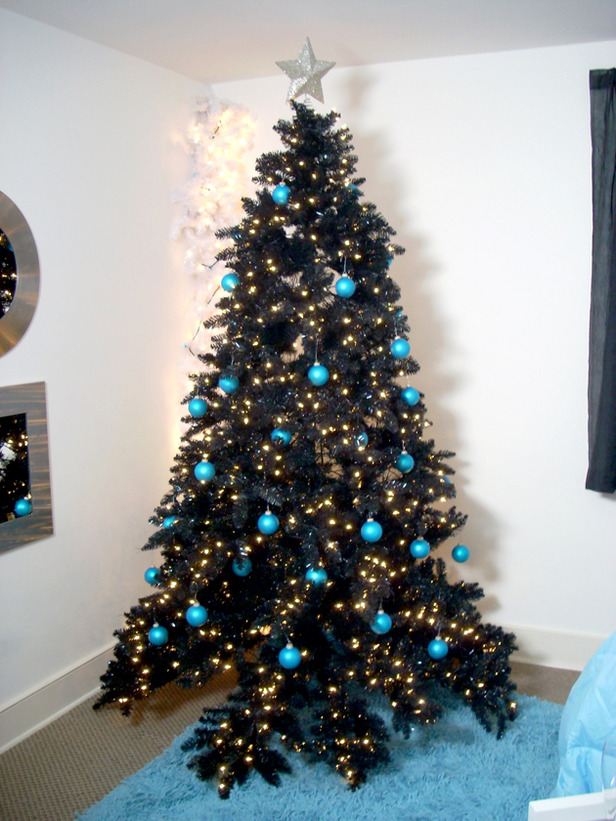 a black tree decorated with lights and turquoise baubles for a contrast