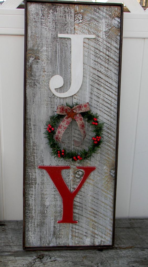 weathered wooden JOY sign with a small wreath