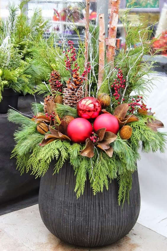 a large urn, evergreens, pinecones, berries, leaves and oversized ornaments