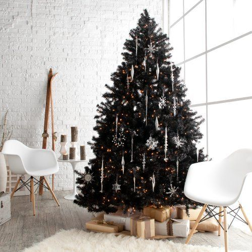 a lush black tree wwith white and silver snowflake ornaments and lights