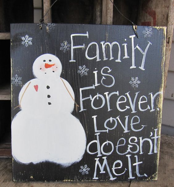 simple and primitive snowman sign on reclaimed wood