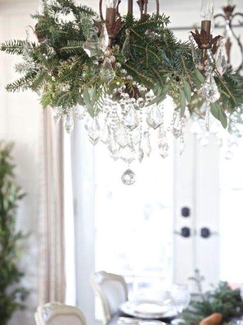 vintage chandelier decorated with foliage, evergreens and crystals