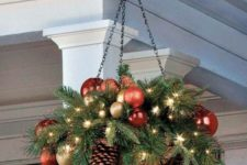 18 a hanging arrangement wwith ornaments, lights and evergreens