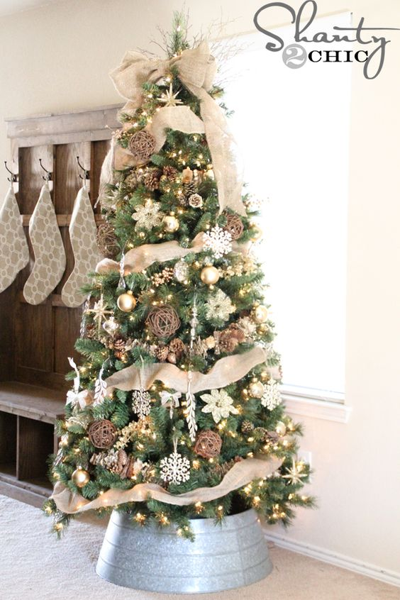 a rustic tree decorated with burlap in a galvanized bucket