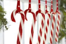 18 candy canes hanging from an evergreen garland are ideal for holidays