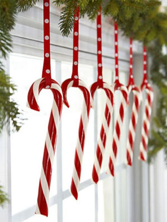 candy canes hanging from an evergreen garland are ideal for holidays