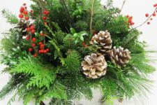 19 a bark wrapped centerpiece with evergreens, branches, berries and pincones