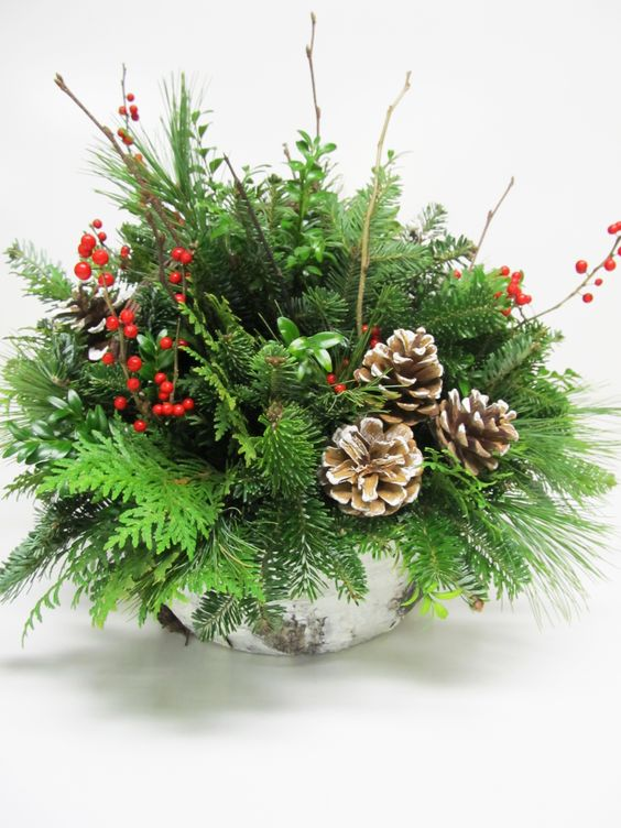 a bark wrapped centerpiece with evergreens, branches, berries and pincones