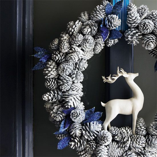 a snowy pinecone wreath with a deer and glitter blue touches