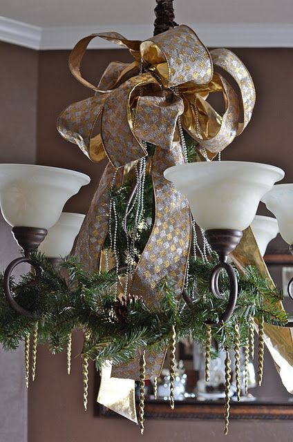 gold and silver ribbon evergreen branches with pinecones to cover a chandelier