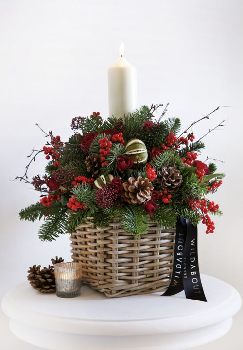 a basket arrangement with pinecones, berries and evergreens
