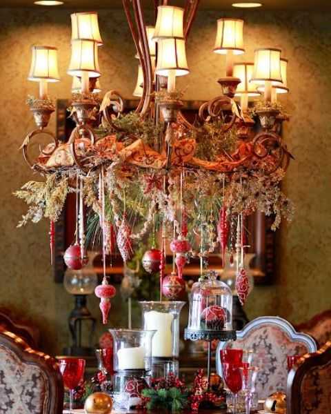 beautiful Christmas chandelier with hanging red ornaments, vintage ribbon and evergreens