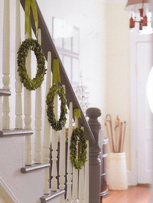 green wreaths hanging from the banister