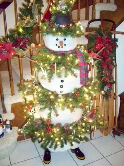 large snowman with fir branches and lights
