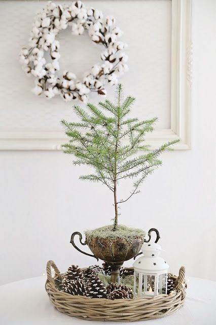 a basket with pinecones, a lantern and a branch, a cotton wreath on the wall