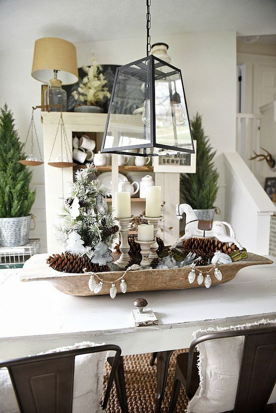 a dough bowl with pinecones, candles and vintage ornaments