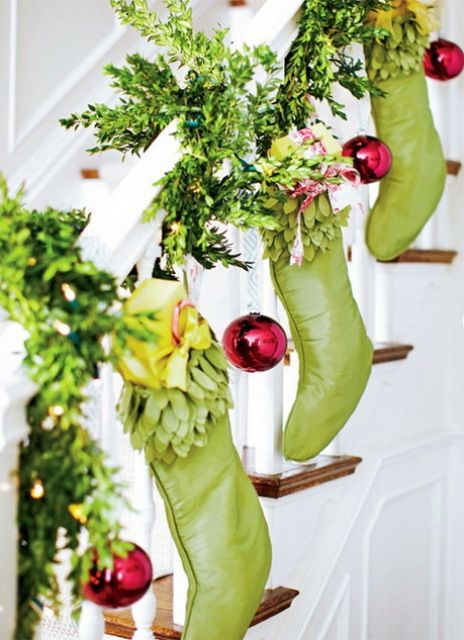 greenery garland wrapping around the banister and green stockings