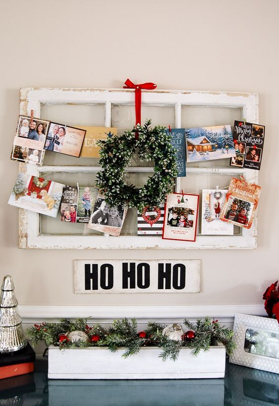 old window frame wwith a mini wreath and cards and pics hanging