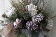 23 a bucket with evergreens, snowy pinecones and flowers