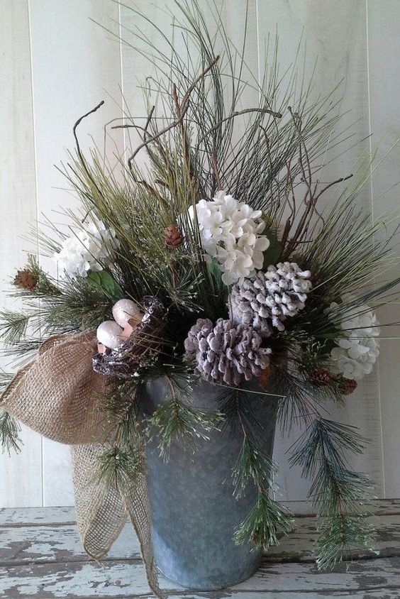 a bucket with evergreens, snowy pinecones and flowers