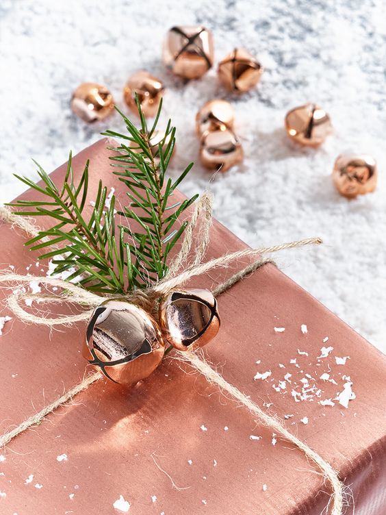 copper gift wrapping and jingle bells and evergreen sprigs for decor