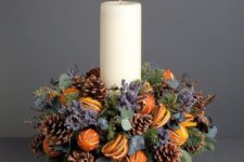 25 a cool centerpiece with a pillar candle, lavender, pinecones and citrus