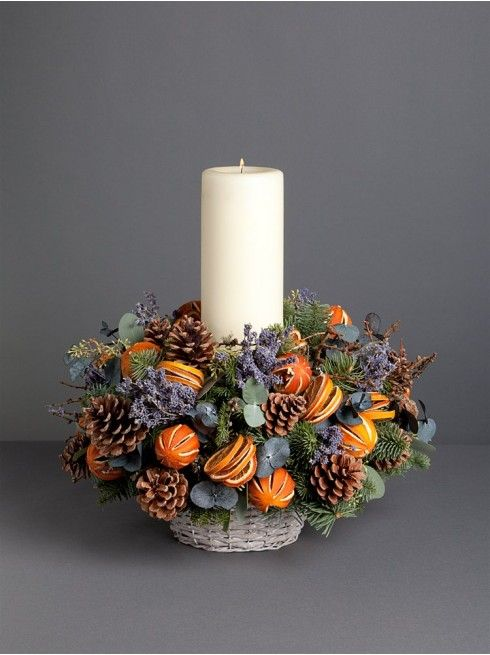 a cool centerpiece with a pillar candle, lavender, pinecones and citrus