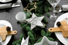 25 a table setting with faux evergreens, star-shaped candle holders and pinecones