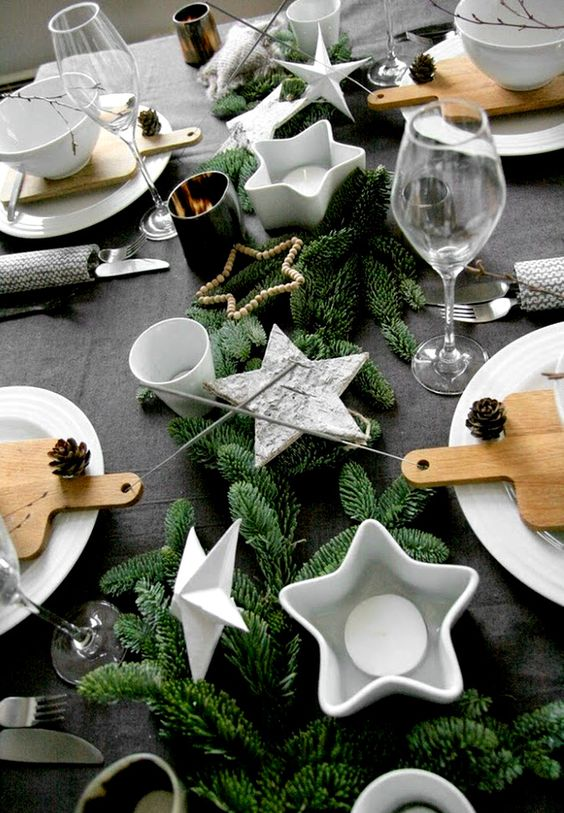 a table setting with faux evergreens, star-shaped candle holders and pinecones