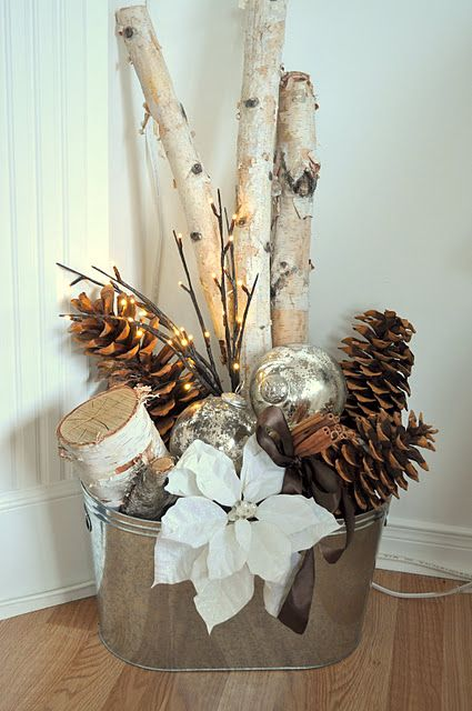 a galvanized bucket with branches, pinecones, ornaments and a poinsettia