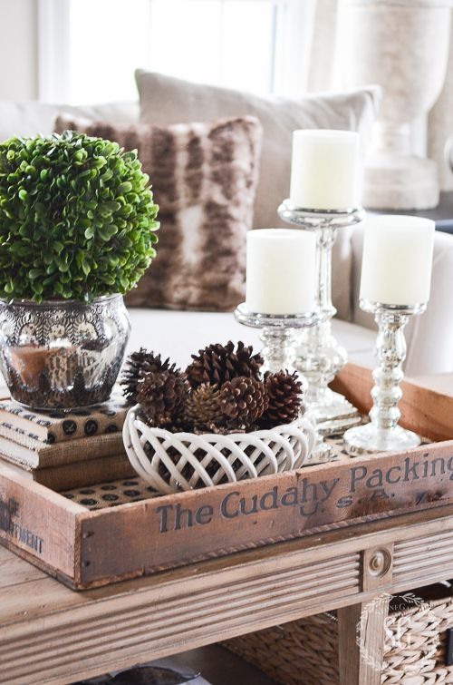 neutral coffee table decor with pinecones, greenery and candles