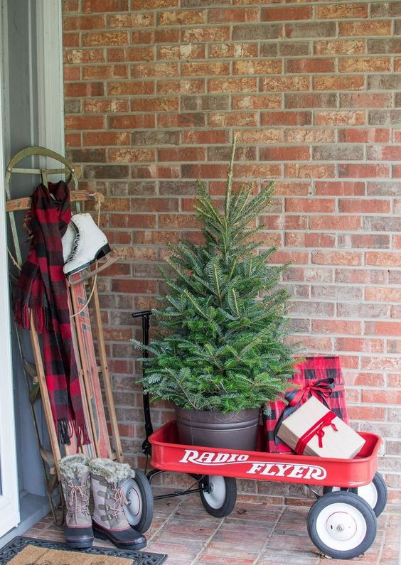 a cart with a fir tree in a bucket, gift boxes and a sleigh