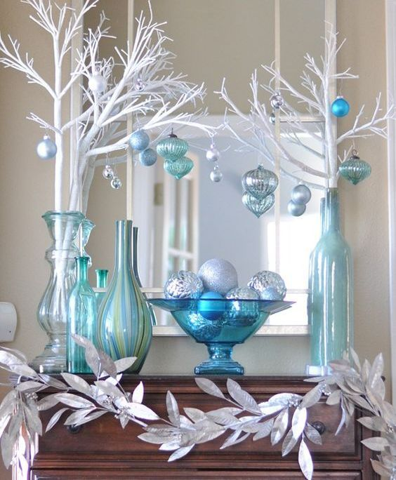 silver, blue and white mantel decor with white branches and leaves
